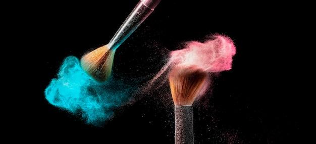Pinceau de maquillage avec de la poudre rose et bleue dispersée.