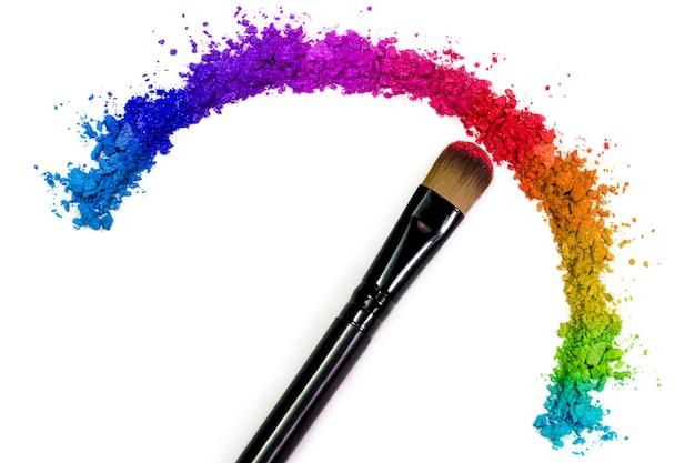 Pinceau de maquillage professionnel sur fard à paupières rouge écrasé
