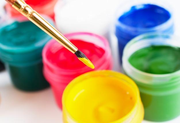 Pinceau et nombreux pots de peinture aux couleurs