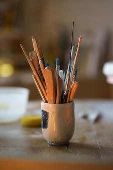 Pinceau avec des outils pour la mise en forme de poterie dans un bol sur un équipement de céramique de table dans un espace d'art créatif