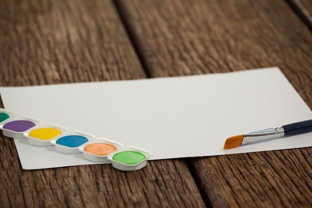 Pinceau, palette aquarelle et papier blanc sur table en bois