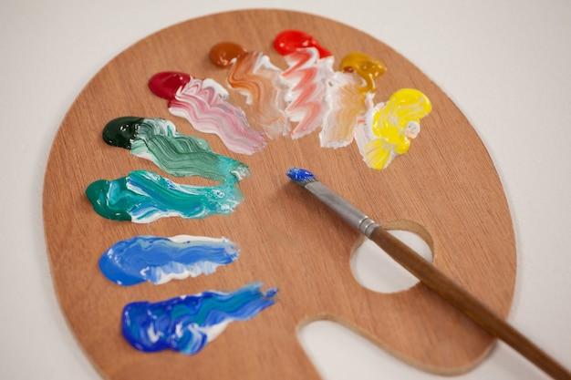 Pinceau et palette contre la surface blanche