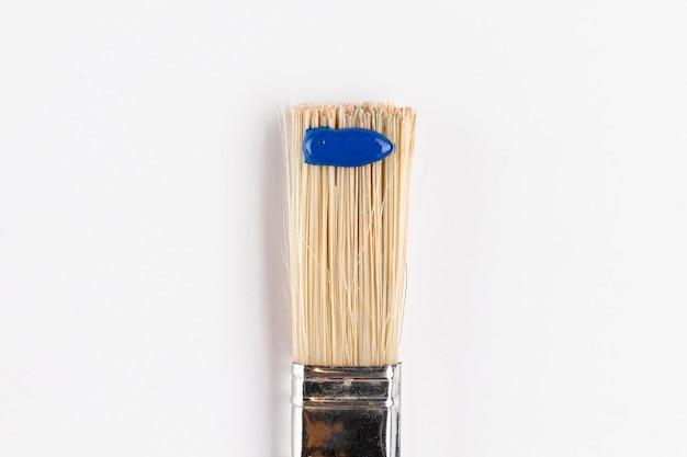 Pinceau avec peinture bleue et fond blanc