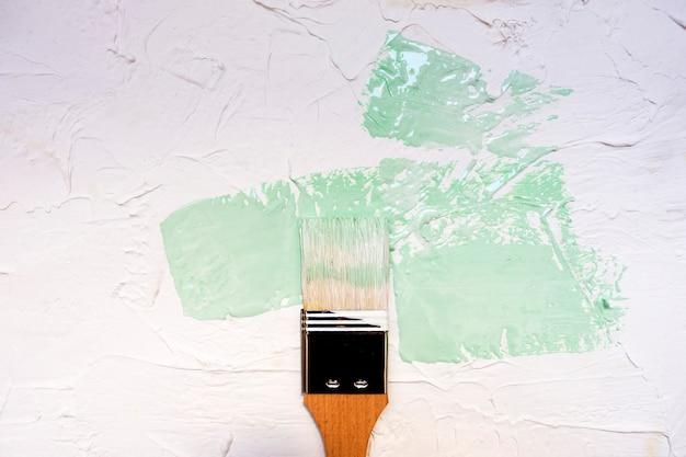 Pinceau avec de la peinture de couleur sur fond de mur blanc
