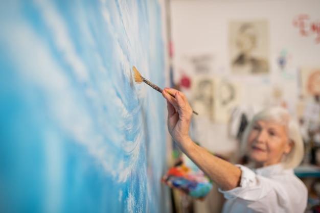 Pinceau de peinture. gros plan d'un artiste talentueux âgé tenant un pinceau et une toile à colorier