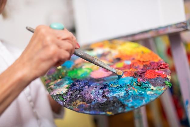 Pinceau de peinture. gros plan d'une femme âgée tenant un pinceau et une palette de couleurs