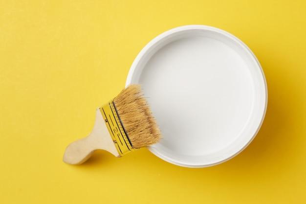 Pinceau et peinture peut avec la couleur blanche sur un fond jaune, vue de dessus