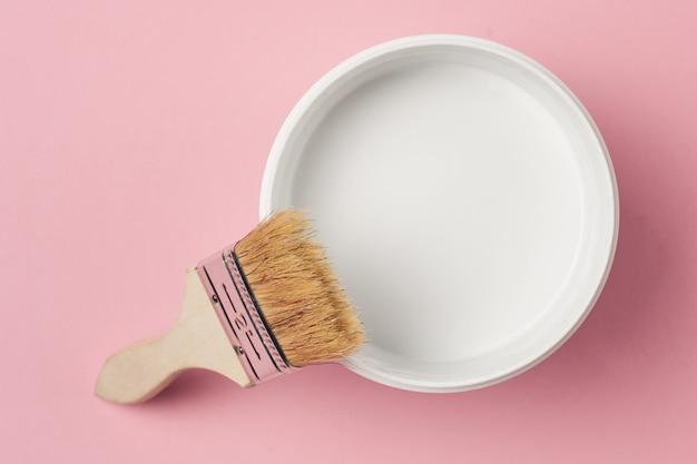 Pinceau et peinture peut avec la couleur blanche sur un fond rose, vue de dessus