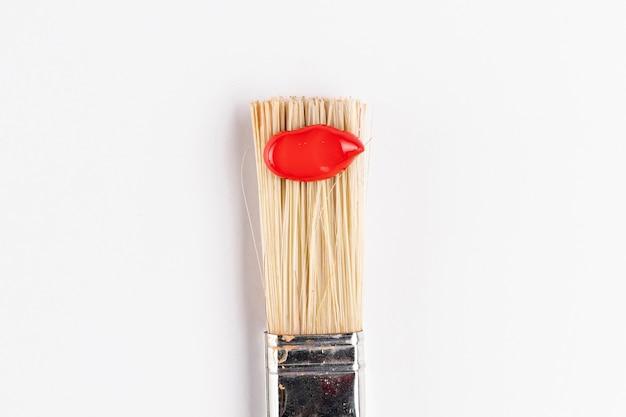 Pinceau avec peinture rouge et fond blanc