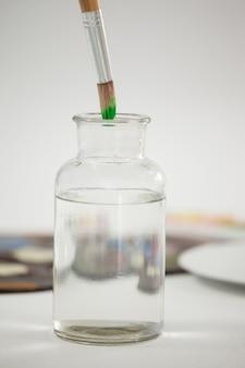 Pinceau avec de la peinture verte trempée dans un pot rempli d'eau sur fond blanc