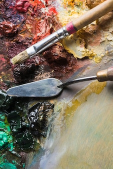 Pinceau prenant la peinture près du couteau à palette