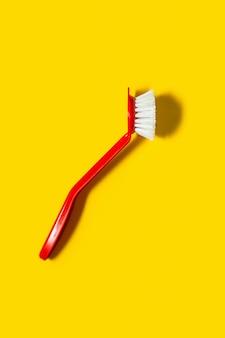 Le pinceau rouge vif se trouve sur un jaune vif. dans le style du pop art. vue de dessus