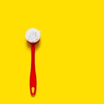 Le pinceau rouge vif se trouve sur une surface jaune vif. dans le style du pop art.