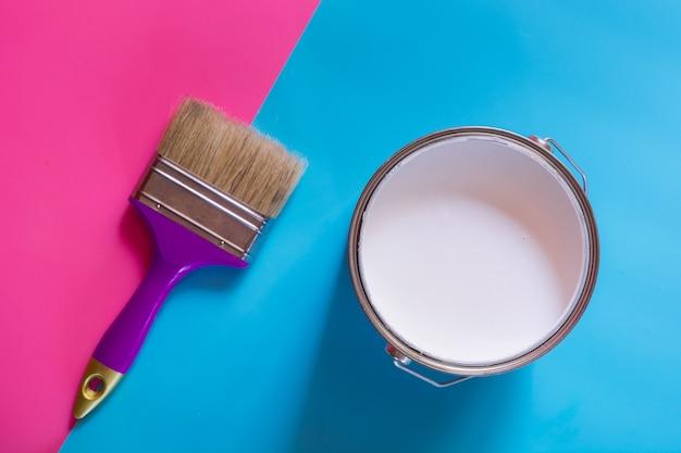Pinceau violet avec un pot ouvert de peinture blanche,