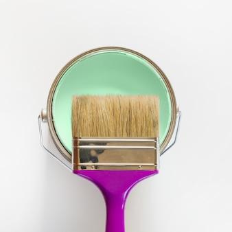 Pinceau violet avec un pot de peinture à la menthe ouvert