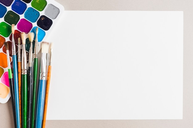 Pinceaux et aquarelle près du papier