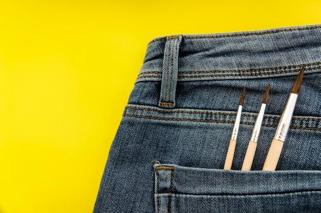 Pinceaux dans la poche arrière du jean bleu pour femme.