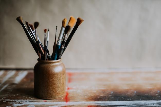 Pinceaux dans un pot en céramique.