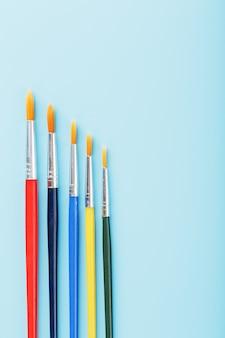 Pinceaux de différentes couleurs pour le dessin, la créativité et l'art sur fond bleu.