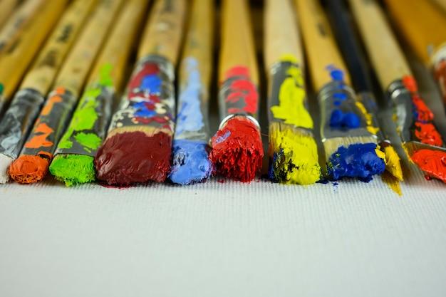 Des pinceaux avec différentes peintures se trouvent sur la toile