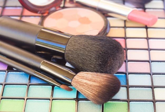 Pinceaux doux avec des ombres à paupières et des cosmétiques de maquillage décoratifs
