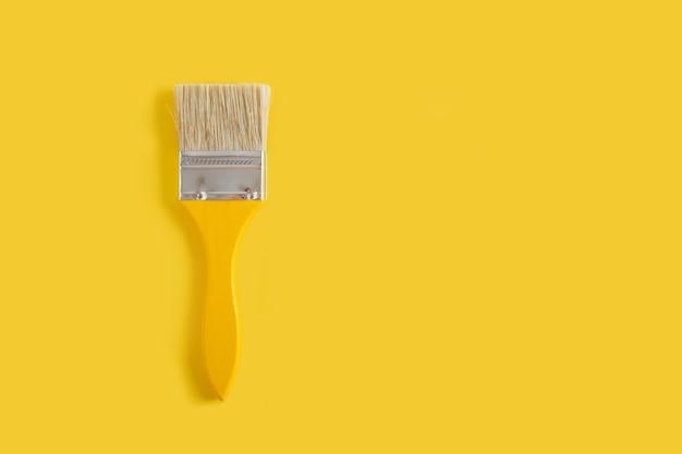 Pinceaux jaunes en bois sur une vue de dessus de l'espace de copie de fond jaune