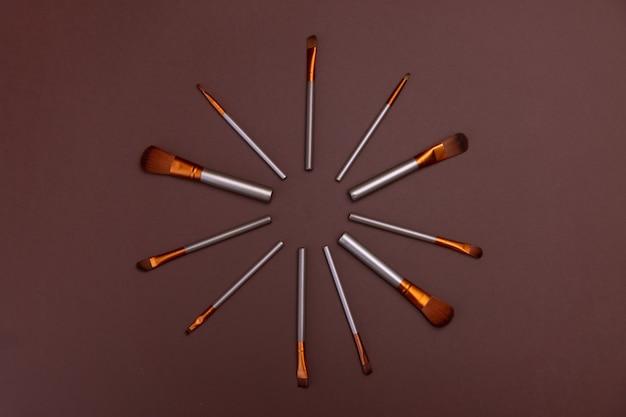 Pinceaux de maquillage cosmétiques sur un fond marron espace copie concept de beauté cosmétique
