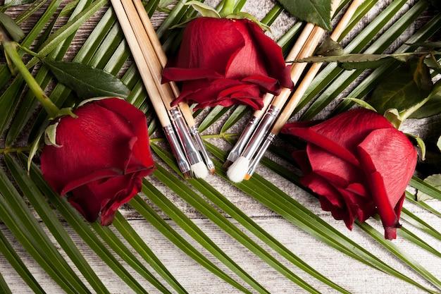 Pinceaux de maquillage à côté de roses sur fond de bois