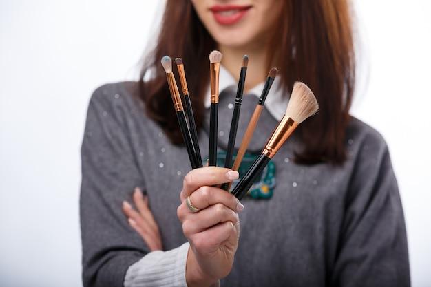 Pinceaux de maquillage dans les mains de la femme. notion de cosmétologie. photo recadrée.