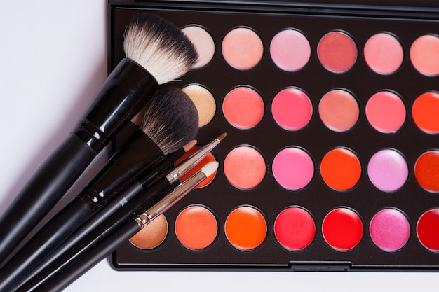 Pinceaux à maquillage dans le support et les cosmétiques isolés on white