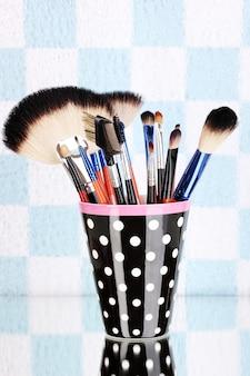 Pinceaux de maquillage dans une tasse à pois noirs sur bleu et blanc