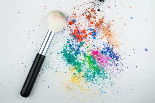 Pinceaux de maquillage sur fond blanc avec poudre de pigment coloré