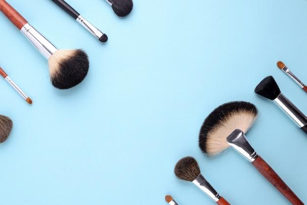 Pinceaux de maquillage sur un fond bleu.