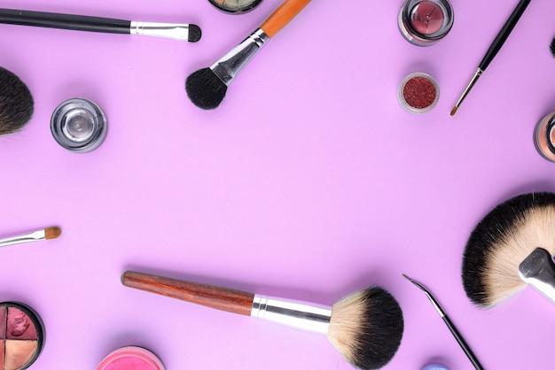 Pinceaux de maquillage sur un fond rose. vue de dessus, pose à plat, espace de copie