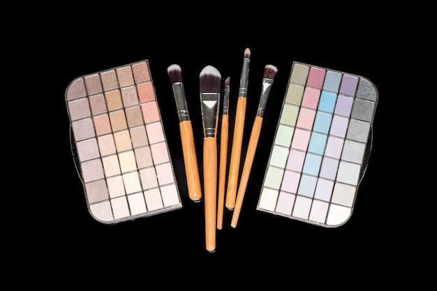 Pinceaux de maquillage et palette d'ombres à paupières maquillage coloré sur une surface noire