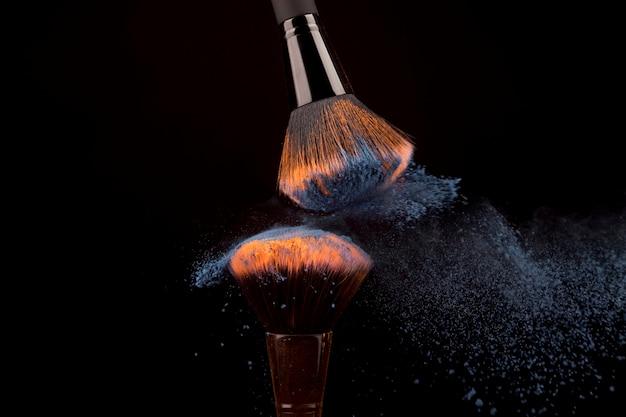Pinceaux de maquillage et poudre brillante sur fond sombre