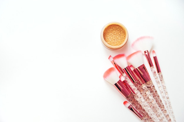 Pinceaux de maquillage et poudre sur fond blanc. mise au point sélective.