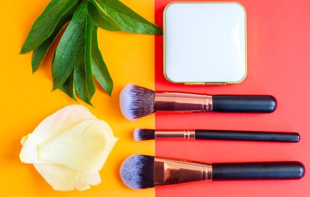 Pinceaux de maquillage premium et fard à joues sur un fond rouge et orange coloré, cosmétiques créatifs à plat, espace de copie