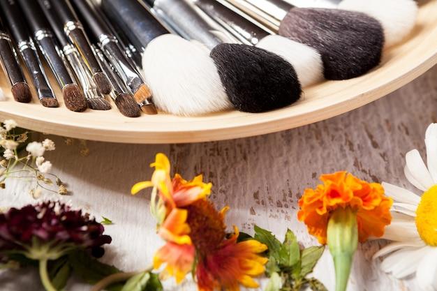 Pinceaux de maquillage professionnels sur plaque à côté de fleurs sauvages sur fond de bois