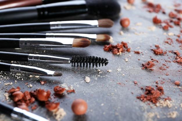 Pinceaux de maquillage et rouges écrasés sur fond gris
