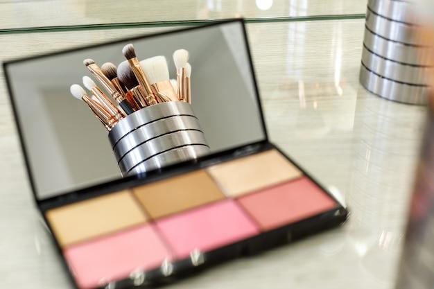 Les pinceaux de maquillage se reflètent dans un miroir de palette avec des ombres