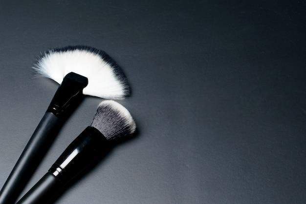 Pinceaux de maquillage sur tableau noir