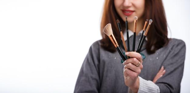 Pinceaux de maquillage visagiste professionnels. notion de cosmétologie. concept de soins de beauté de la peau. style de mode féminin. la fille a les cheveux longs. maquillage et cosmétiques.