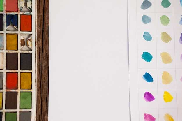 Pinceaux, palette et papier blanc sur table en bois