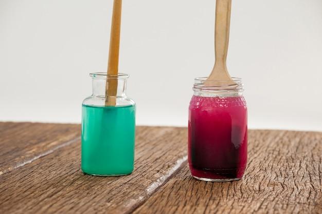 Pinceaux avec de la peinture bleue et rouge trempés dans l'eau