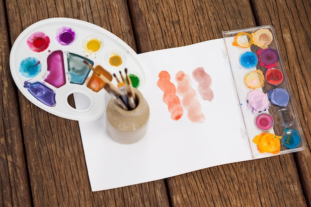 Pinceaux, peintures à l'aquarelle, palette de verre et papier blanc sur table en bois