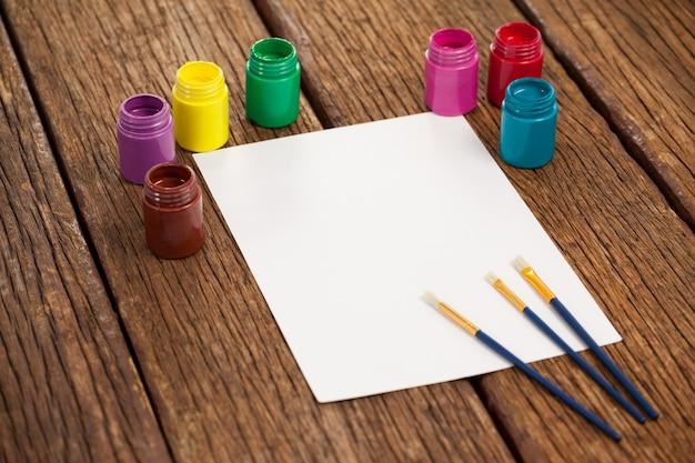 Pinceaux, peintures à l'aquarelle et papier blanc contre une surface blanche