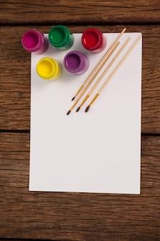 Pinceaux, peintures aquarelles et papier blanc sur table en bois