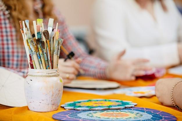 Les pinceaux et les peintures des mains des femmes s'appuient sur une formation artistique pour créer le mandala de la vie