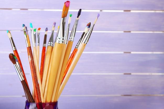 Pinceaux avec peintures sur mur en bois